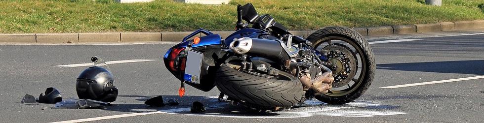 Photographie représentant une moto et des équipements de sécurités abandonnés sur la route suite à un accident de la circulation