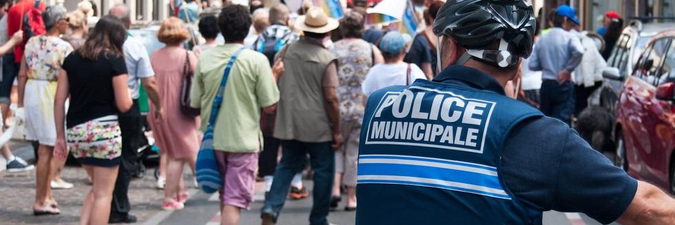 Photographie montrant un policier municipal à vélo encadrant une manifestation