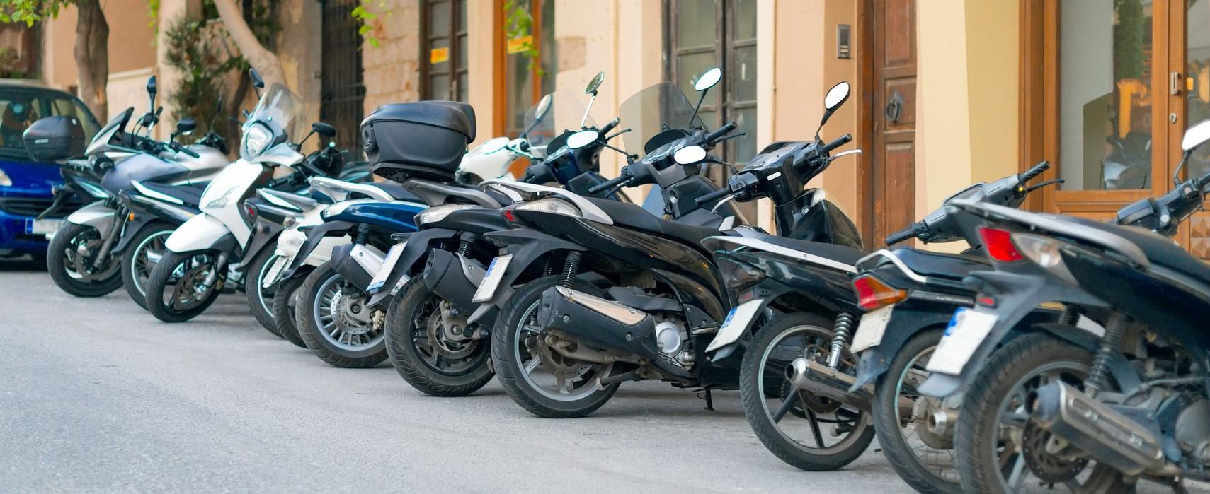 Photographie montrant des scooters garés sur un parking.