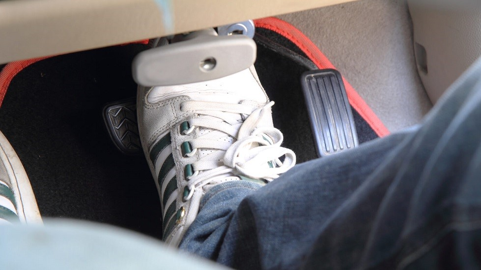 Automobiliste portant une paire de baskets