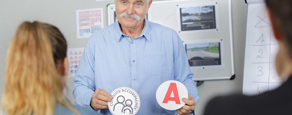 Instructeur de la conduite tenant des stickers de jeune permis et de conduite accompagnée