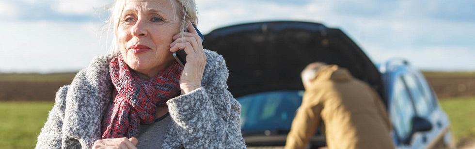 Couple de seniors appelant leur assurance suite à une panne de voiture