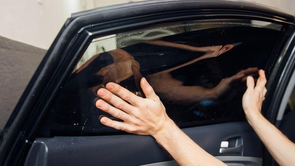 Pose d'un filtre solaire sur les vitres laterales d'une automobile