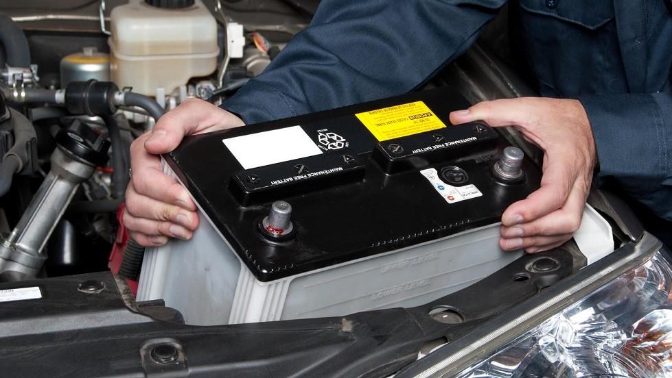 Mecanicien retirant la batterie d'une automobile