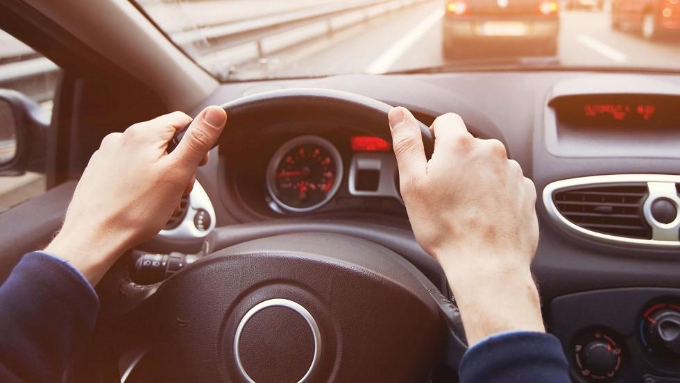Conducteur tenant le volant de son automobile