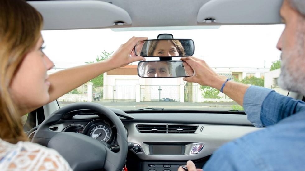Instructeur et candidate a l'examen du permis de conduire ajustant leur retroviseur