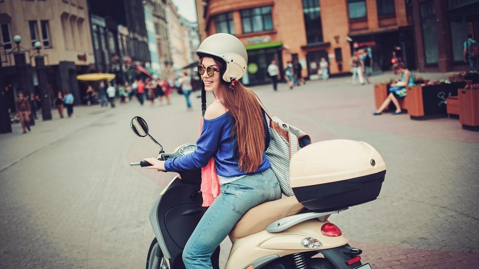 Jeune femme conduisant un scooter en agglomeration