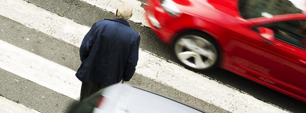 Un vieil homme traversant un passage piéton alors que des véhicules continuent de circuler.