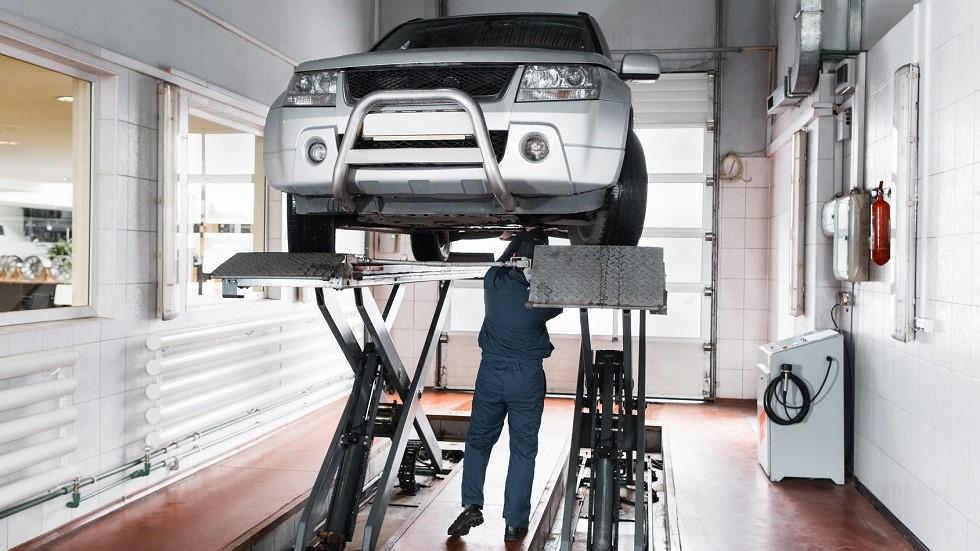 Garagiste travaillant sur une automobile positionnee sur un pont mobile