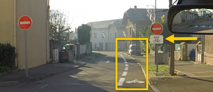 Photographie montrant une piste cyclable vue depuis l'habitacle d'un véhicule.