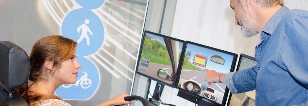 Instructeur donnant des directives à une candidate s'entraînant sur un simulateur à la conduite