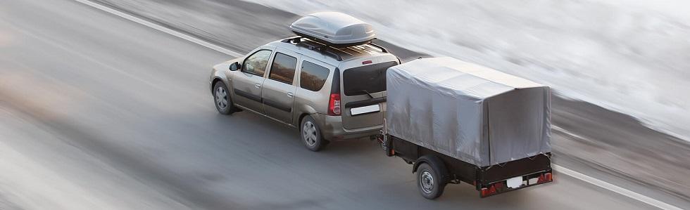 Photographie d'une voiture tractant une remorque.