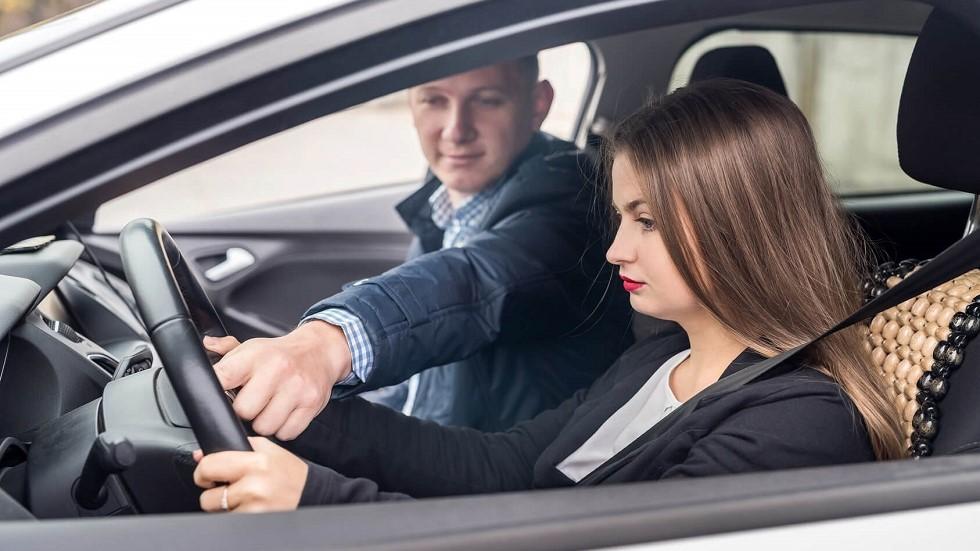 Examinateur du permis attrapant le volant d'une candidate