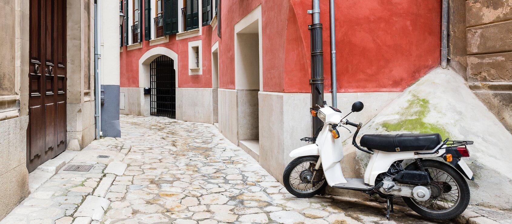Photographie montrant un scooter stationné à l'entrée d'une ruelle.