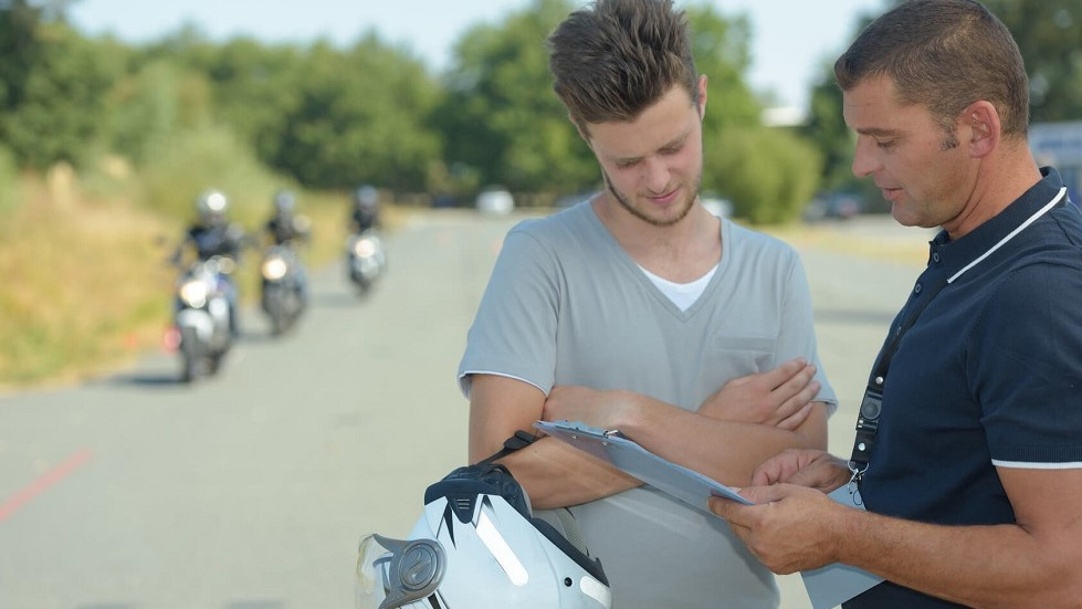 Enseignant de la conduite expliquant au candidat le deroulement du permis moto