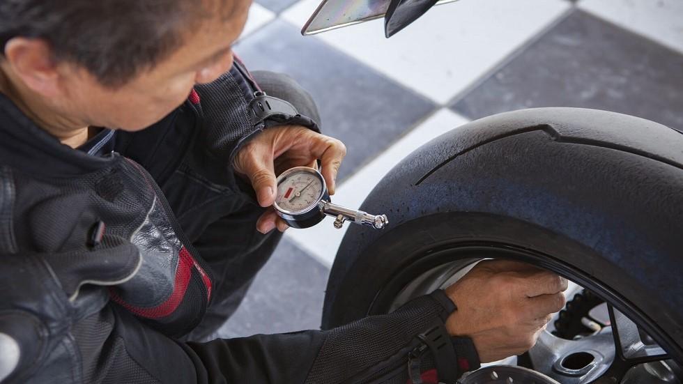 Motard vérifiant la pression de ses pneumatiques