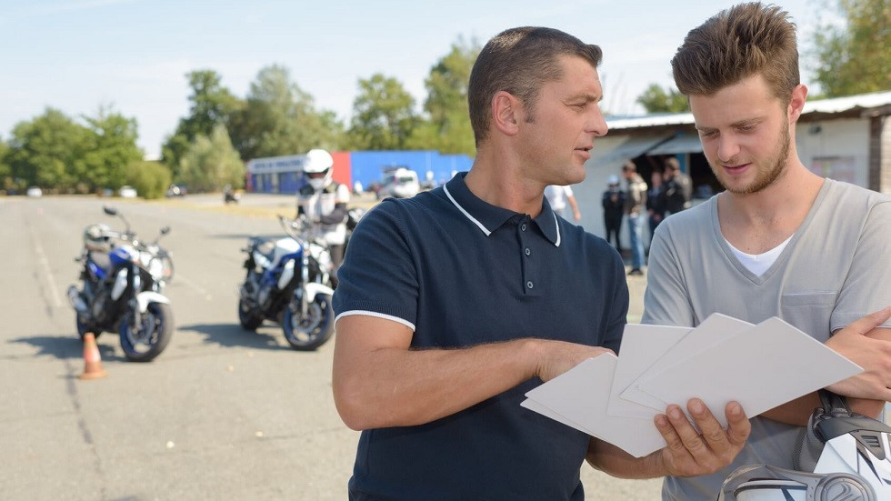 Enseignant de la conduite presentant les fiches du permis moto a un candidat