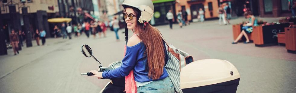 Jeune femme conduisant un scooter