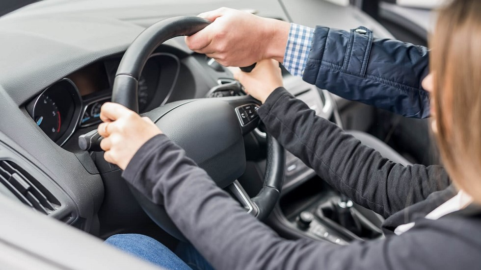 Examinateur du permis de conduire redressant le volant d'une candidate
