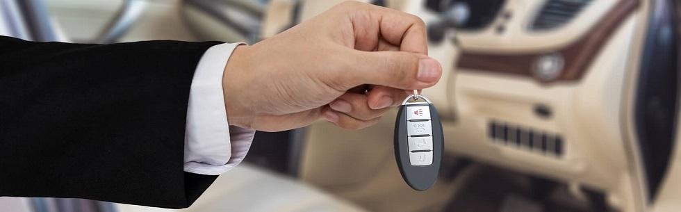 main d'un vendeur de voitures tenant une clé de voiture neuve