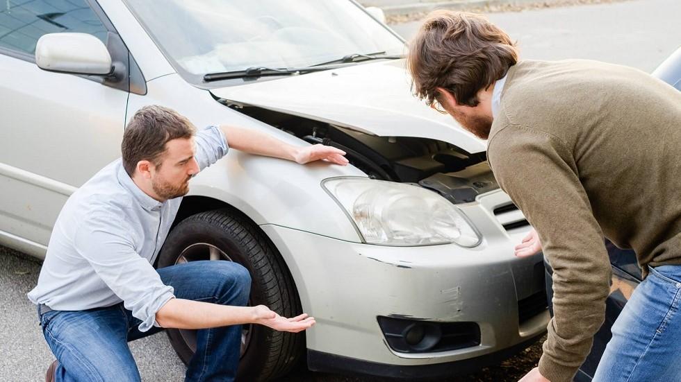 Usagers de la route constatant des degats sur une voiture