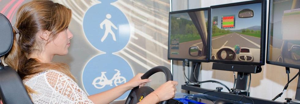 Photographie montrant une jeune femme s'entraînant à la conduite grâce à un simulateur