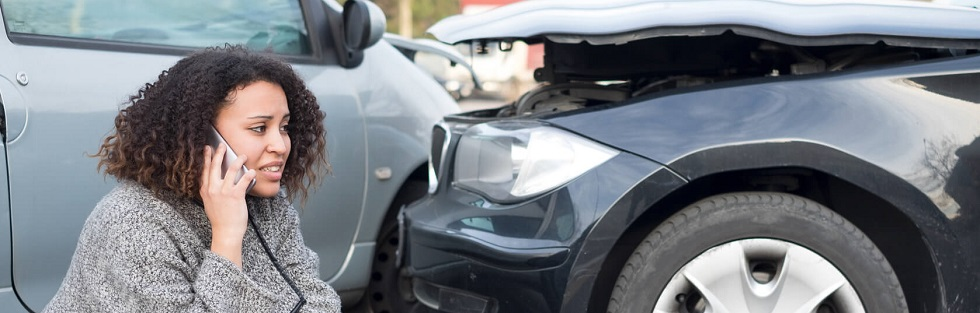 Jeune automobiliste appelant son assurance suite à un accident de la route