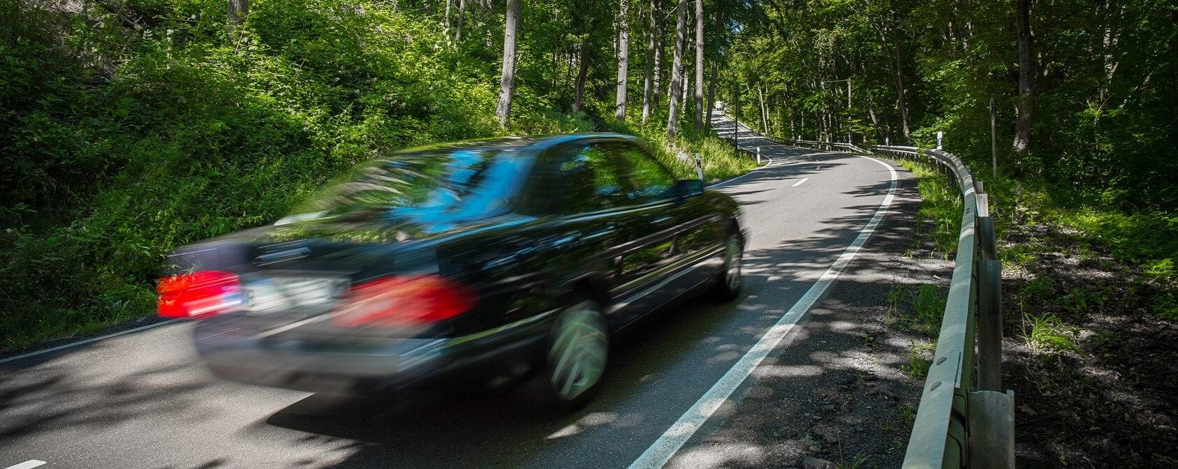 Photographie montrant une voiture en roulant le long d'une route forestière.