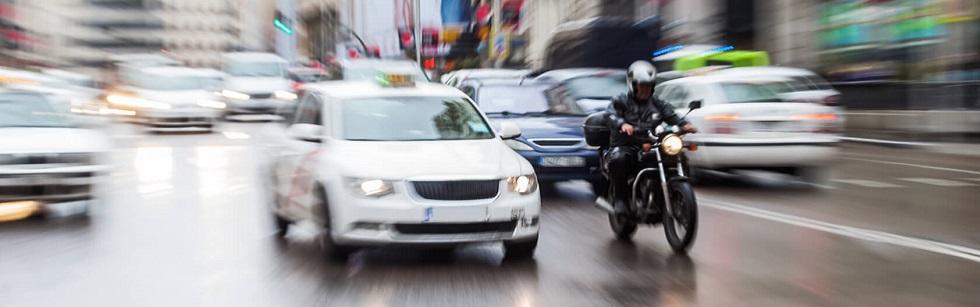 Photographie montrant un motard circulant en ville par temps de pluie
