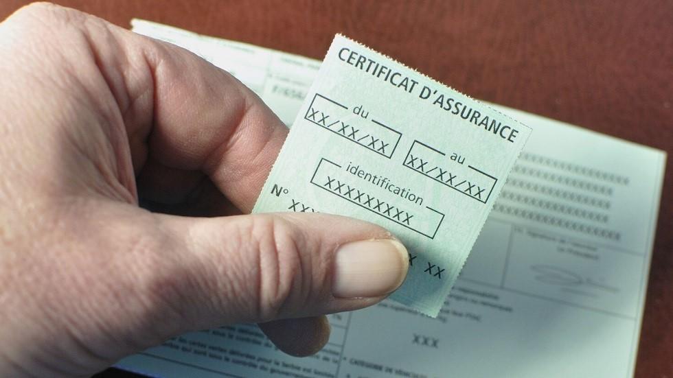 Usager de la route tenant son certificat d'assurance dans sa main