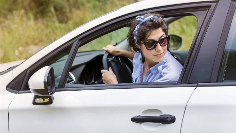 Jeune conductrice garant son automobile en marche arriere