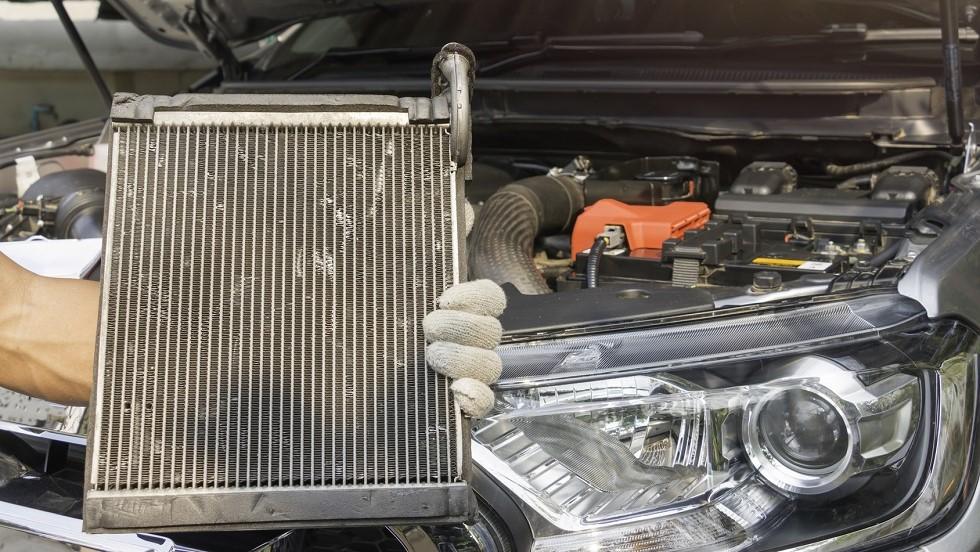 Garagiste tenant le radiateur d'une automobile