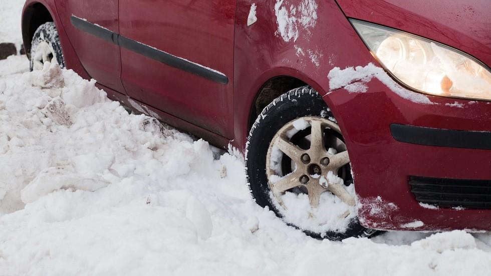 Roues braquees d'une automobile coincee dans la neige
