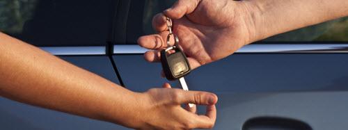 Photographie d'un conducteur donnant ses clés de voiture à un autre.